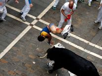 A runner gets tossed in the air after getting gored during the sixth running of the bulls of the San Fermin festival in Pamplona