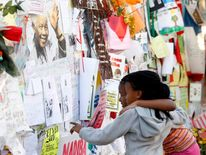 Well-wishers view messages of support left outside the hospital where Mandela is being treated in Pretoria