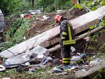 A firefighter stands next to the wreckage of a bus which crashed near Avellino