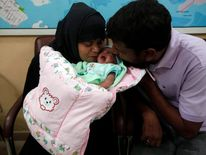 Childless couple kisses their newly adopted daughter, Fatima, whom Pakistani television talk show host Hussain gave them on his show, in Karachi