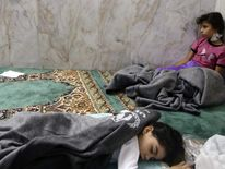 Girls who survived from what activists say is a gas attack rest inside a mosque in the Duma neighbourhood of Damascus