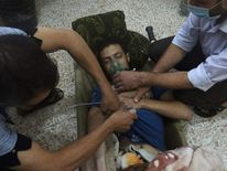 A man, affected by what activists say is nerve gas, breathes through an oxygen mask in the Damascus suburbs of Jesreen