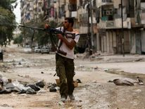 A Kurdish Free Syrian Army fighter fires his weapon in Ashrafieh, Aleppo