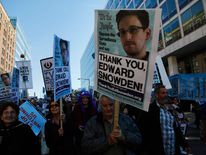 Demonstrators hold signs supporting former NSA contractor Snowden pitol in Washington on October 26, 2013