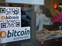Signs on window advertise the new Bitcoin ATM at Waves Coffee House in Vancouver, Canada