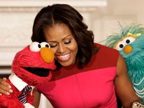 Michelle Obama hugs Sesame Street characters Elmo and Rosita
