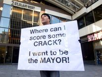 Nic Bibassis holds a sign as Toronto Mayor Rob Ford attends his weekly radio show in Toronto