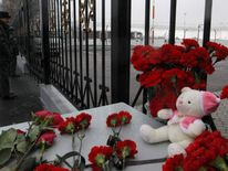 Flowers and a teddy bear are left near a fence of Kazan airport