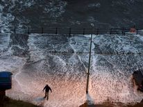 A man stands in water washed onto the promenade of the north bay in Scarborough, northern England