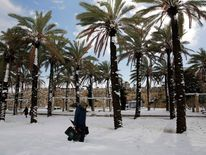A man walks through snow near Jerusalem's Old City walls