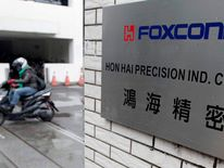 A motorcyclist rides past the entrance of the headquarters of Hon Hai, which is also known by its trading name Foxconn, in Tucheng, New Taipei city