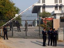 Police officers stand guard at the gate of the Special Court in Islamabad