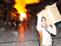 A man carrying his belongings, runs away from a fire at the Dukezong Ancient Town in Shangri-la county