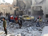 People search for survivors amid damage caused by what activists said was an air strike by forces loyal to Syria's President Assad in the Al-Sakhour neighbourhood of Aleppo