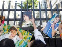 Fans of singer Justin Bieber hold up posters, in an alley behind the hotel where Bieber is presumed to be staying, in Miami Beach