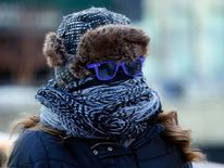 A commuter braves the cold weather while walking the streets of Chicago, Illinois