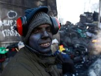 An anti-government protester poses for a picture at the site of clashes with riot police in Kiev