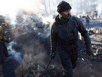 Anti-government protesters work on barricades at the site of clashes with riot police in Kiev
