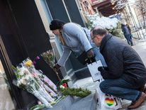 Passersby leave flowers on a makeshift memorial for actor Philip Seymour Hoffman in front of his apartment building in the Manhattan borough of New York