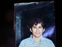 The father of castaway fisherman Jose Salvador Alvarenga shows a picture of his son in their fishing hometown of Ahuchapan