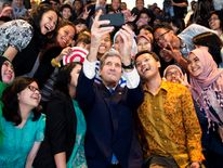 U.S. Secretary of State Kerry takes a selfie with a group of students before delivering a speech on climate change in Jakarta