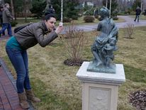 A woman takes a picture of a statue in the grounds of the residence of Ukraine's President Viktor Yanukovych.