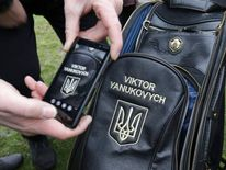 A man takes a picture of a golf bag in the grounds of the Mezhyhirya residence of Ukraine's President Viktor Yanukovych.