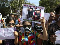 Protesters hold pictures of Zaw Lin and Win Zaw Htun, two Myanmar migrant workers in Thailand, as they protest in front of the Thai embassy in Yangon