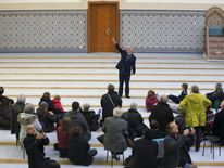 People listen to the explanations of guide Mohamed Latahi (C), as they visit the Strasbourg Grand Mosque