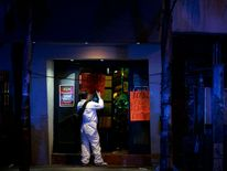 Member of a forensic team takes photos outside a bar at a crime scene, after an attack by unidentified gunmen in downtown Guadalajara