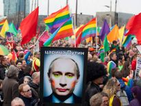 A demonstrator holds up a picture depicting Russian President Putin with make-up during a protest by the gay community in Amsterdam