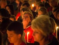 A woman mourns during a candle light church service at St Mary's for victims of a fertilizer plant explosion in the town of West