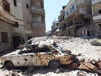 A destroyed car is seen on a street lined with buildings damaged by what activists said was shelling by forces loyal to Syria's President Assad in Homs