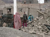 An Iranian family walk amidst the rubble of a building in the eastern village of Shaj after an earthquake