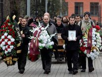 Friends and relatives take part in the funeral ceremony of Magnitsky at a cemetery in Moscow