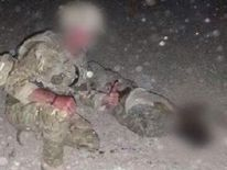 Photo appears to show at least one UK serviceman posing with a dead Taliban fighter
