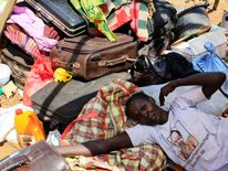 A mother displaced by recent fighting in South Sudan rests on top of her belongings inside a makeshift shelter at the UNAMIS facility in Jabel