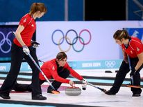 Eve Muirhead of Great Britain (C) plays the final stone alongside Claire Hamilton (L) and Vicki Adams (R) during the Bronze medal match