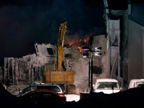 Heavy equipment demolishes the wall of the seniors residence Residence du Havre after a fire in L'Isle Verte