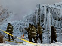 Police officers walk past the Residence du Havre after a fire in L'Isle Verte, Quebec