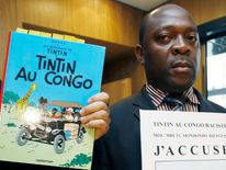 Mondondo holds a placard showing a drawing from the Tintin comics which reads 'Tintin in Congo racist, i accuse' at the Palace of Justice in Brussels