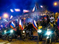 Motorcyclists have Russian flags attached to their bikes as they arrive on Lenin Square before the announcement of preliminary results of today's referendum in Simferopol