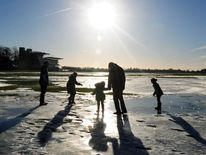 People walk on frozen flood water at York Racecourse, North Yorkshire
