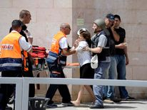 A woman is escorted from the bank in Be'er Sheva