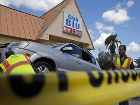 A car hit by gunfire is removed from outside Club Blu