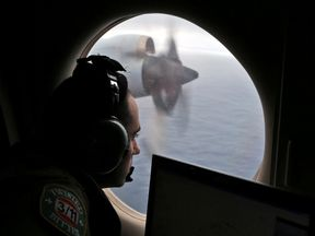A navigator looks out his the plane window on the search for the plane