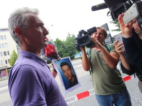 The father of one of the victims at the scene of the shooting holding a picture of his son