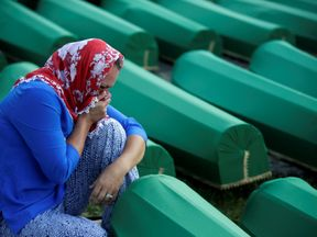 A woman cries cry near coffins of newly identified victims of the 1995 Srebrenica massacre in Potocari near Srebrenica, Bosnia and Herzegovina