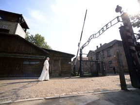 Pope Francis walks through the entrance of Auschwitz