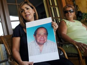 A woman shows a photo of her late father who died after taking the medicine